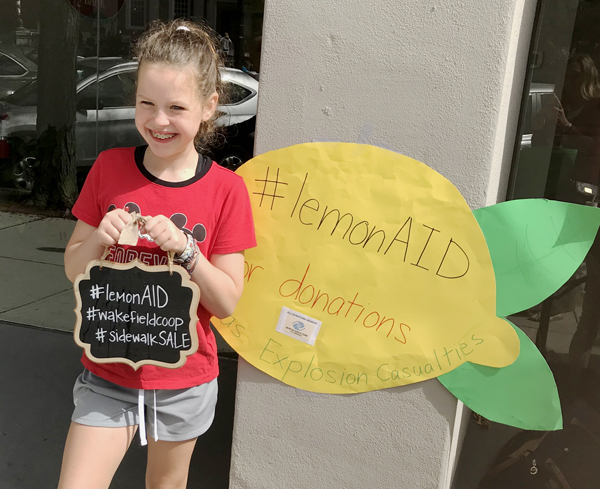 Young girl holding lemonade sign