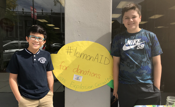 Students standing by lemonade sign